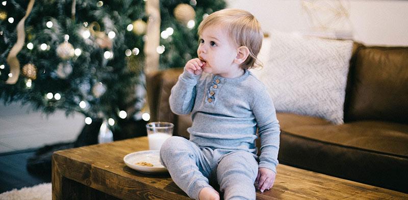 Enfant en pyjama gris, assis sur une table basse en bois devant un sapin de Noël illuminé, en train de prendre son goûter : des gâteaux sucrés et un verre de lait. La santé des enfants passera par l'éducation alimentaire.