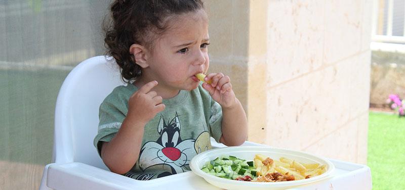Éducation alimentaire : Photographie d'une petite fille assise dans une chaise haute Ikea blanche, qui prend son repas avec les mains
