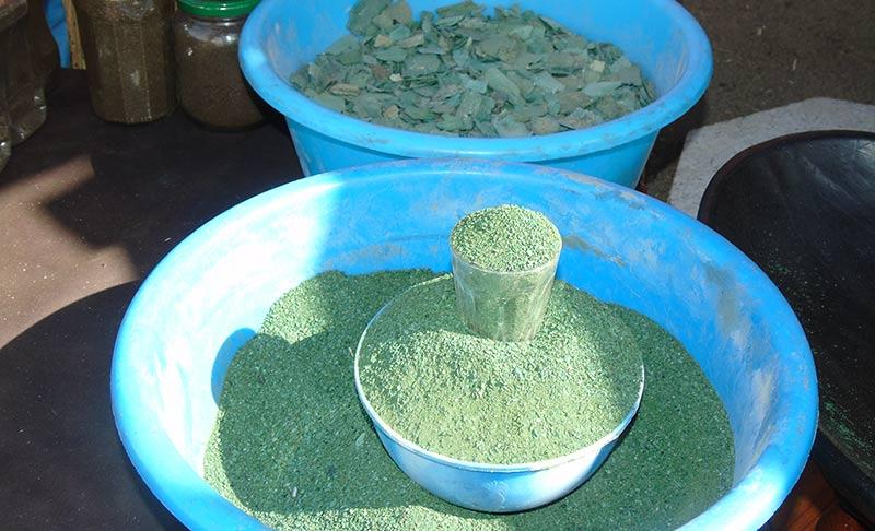 Poudre d'algue verte en vrac dans une bassine bleue, vendue en Afrique