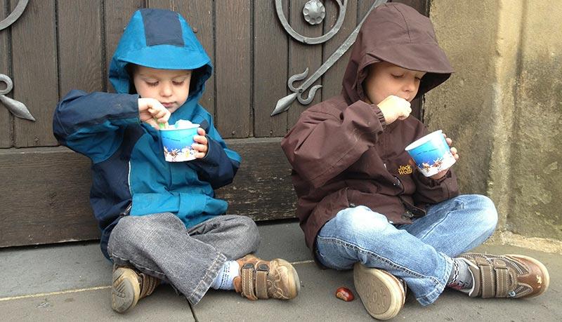 Photographie de deus enfants assis en tailleur dans la rue devant une porte en bois, habillés de jeans et d'anorak à capuche, en train de manger une glace dans un petit pot bleu.