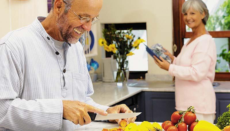 Photographie d'un homme cuisinant un régime alimentaire adapté, spécial contre l'arthrose. Il découpe des légumes crus et colorés sur une planche, pendant que sa femme retraitée le regarde. Mangez mieux, bougez plus pour dire Stop Arthrose !
