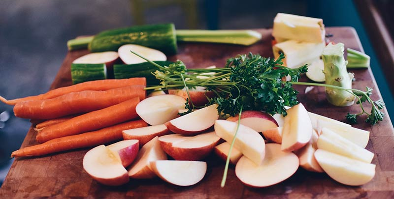 Aliments crus découpés sur une planche en bois : alimentation crue, rawfood, crudivorisme, interview radio sur les dangers de ce régime alimentaire