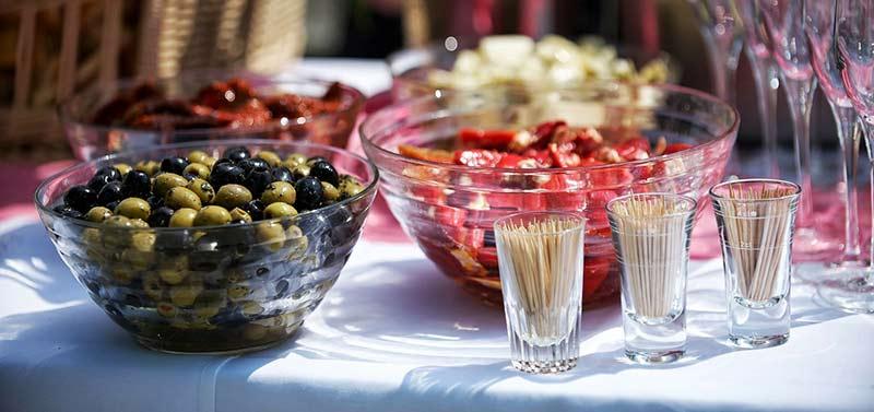 Photographie couleur d'un buffet apéritif posé en extérieur, contenant un saladier d'olives vertes et noires et différents légumes marinés, ainsi que des verres à champagne et des cure-dents.