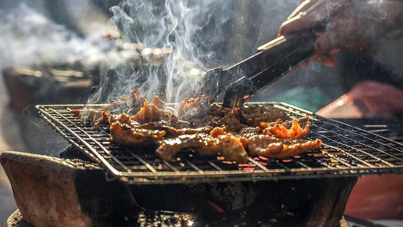 Photographie couleur d'une personne en train de faire griller de la viande sur un barbecue, ce qui génère de la fumée.