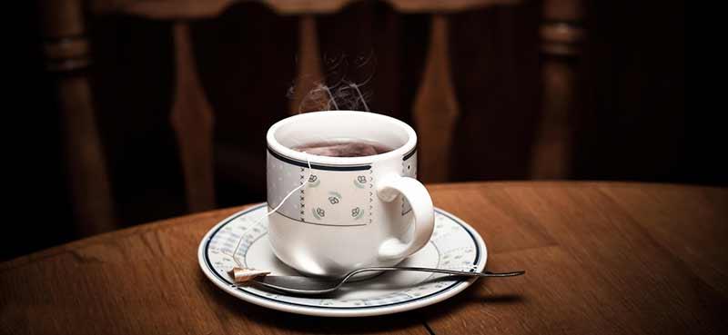 Le thé peut entraîner des carences nutritionnelles en fer en raison des tanins qu'il contient. Photographie d'une tasse de thé chaud fumant sur une table en bois.