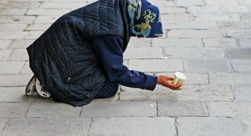 povera mendicante che recita il rosario