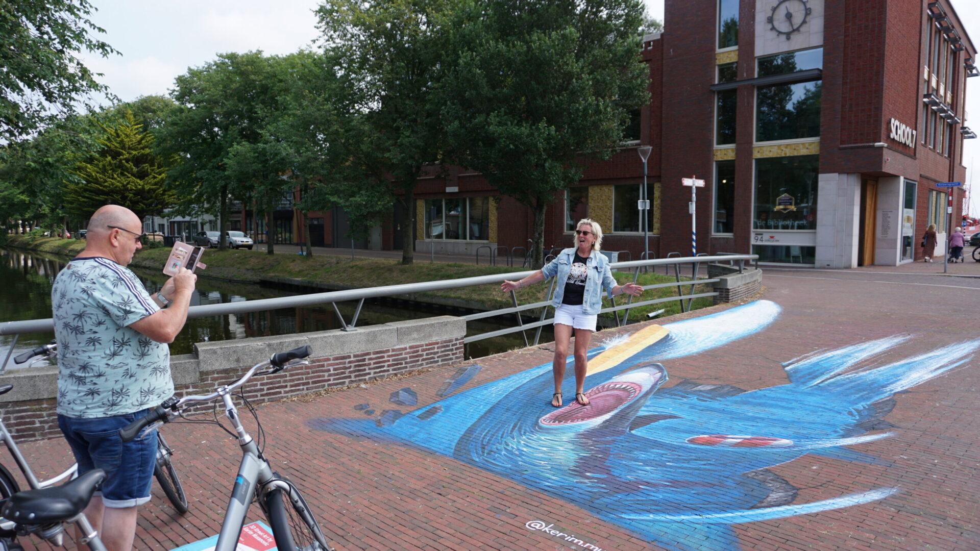 Twee passanten maken een foto bij het schilderwerk op de Keizersbrug