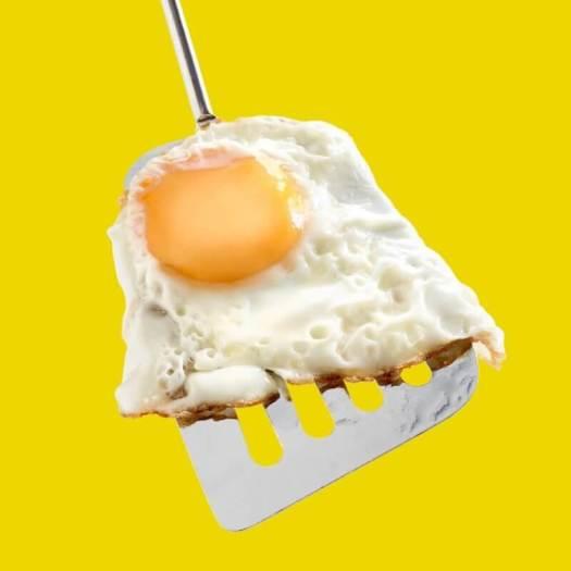 61393769 - fried egg, whole egg yolk on metallic spatula, yellow background