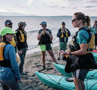 Group of paddlers on a beach talking together before taking off into the ocean.