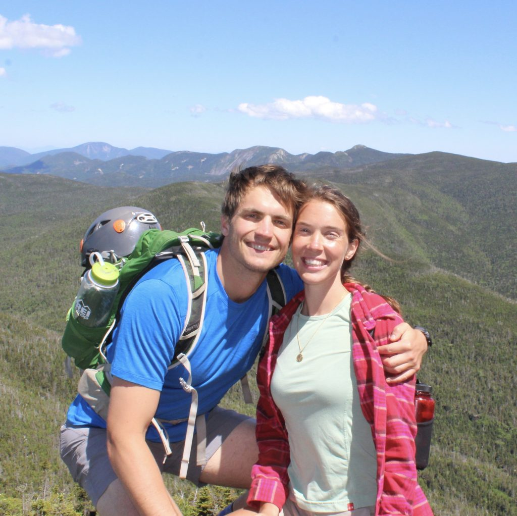 The couple hugs while wearing climbing gear in fronts of a backdrop of green mountains.