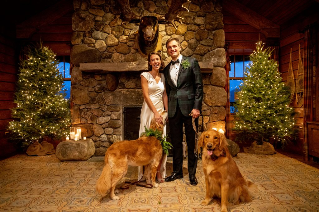 The couple on their wedding day with two golden retrievers in front of a stone fireplace.