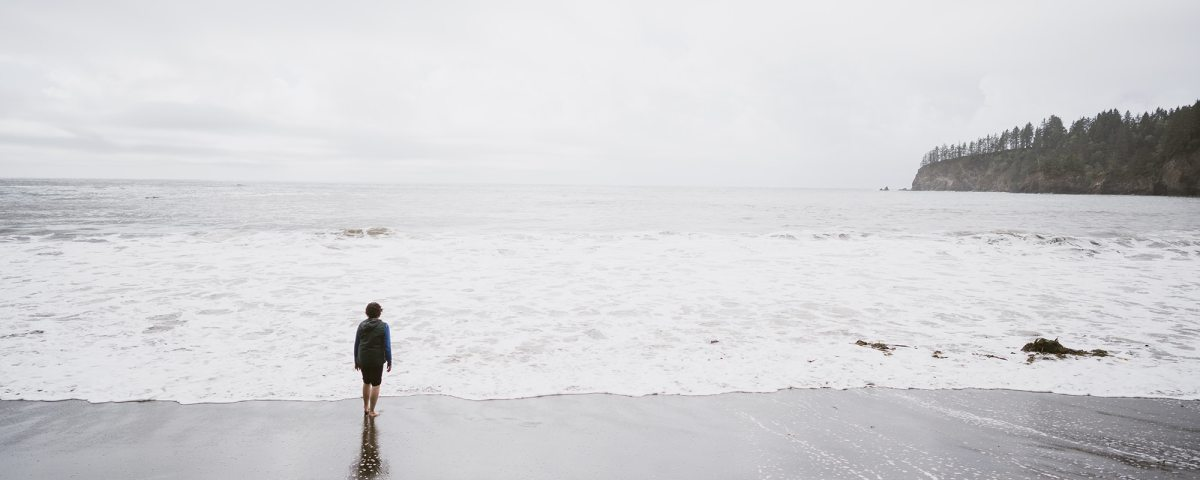 A person stands before a grey sky over a grey ocean.