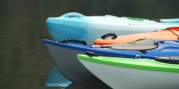 Close-up photo of the bows of four kayaks on the water.
