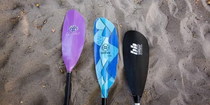 three kayak paddles of varying lengths
