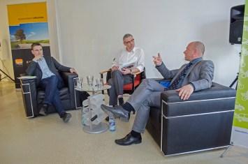 Stephan Kühn, MdB, Bündnis 89/Die Grünen (links), Clusterteamleiter Elektromobilität und Moderator Christian Grötsch (mitte) und Dr. Thomas Feist, MdB, CDU auf dem Podium