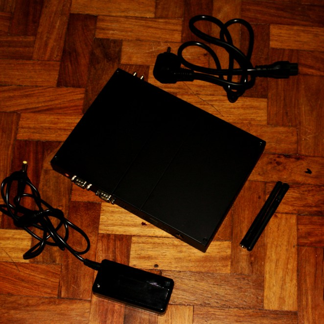 The box comes with a power cord and two antennas. Additional items: User Manual and Drivers (not included in photo)