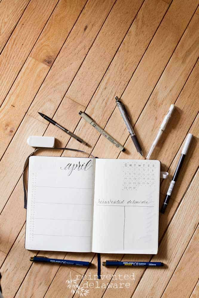 bullet journal showing monthly layout with pens