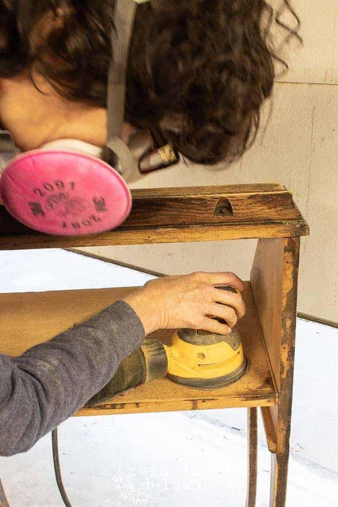 lady sanding a fold down secretary desk with DeWalt orbital sander