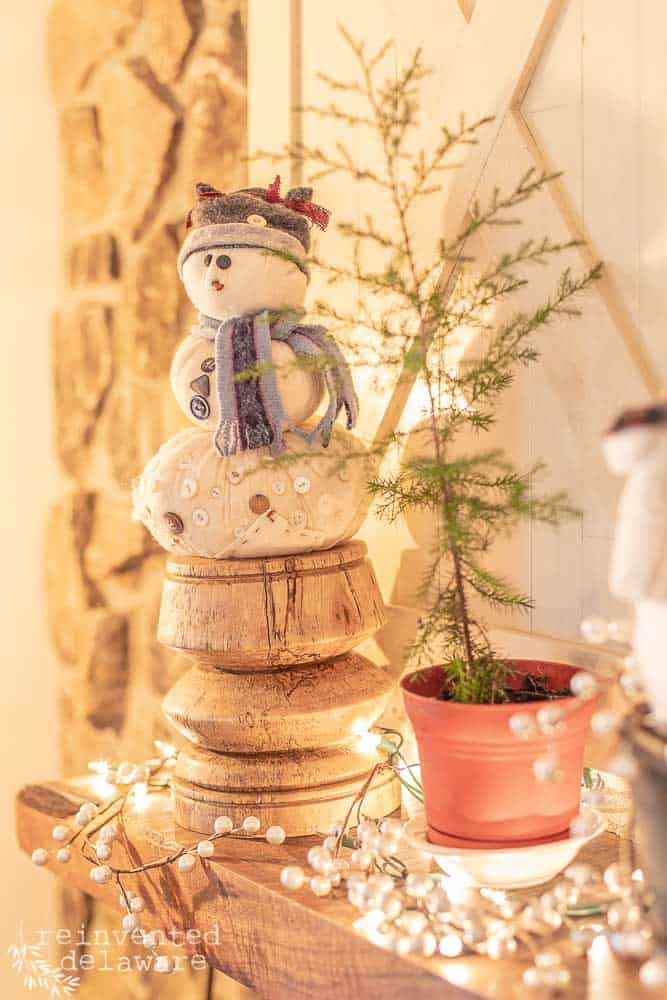 handmade snowman on mantle with spruce sapling in potted container