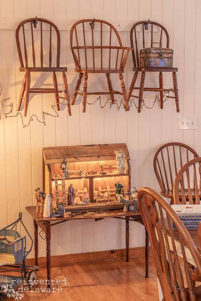 children's chairs hanging on a wall with bell garland hanging from chairs. nativity scene below chairs on a small vintage table