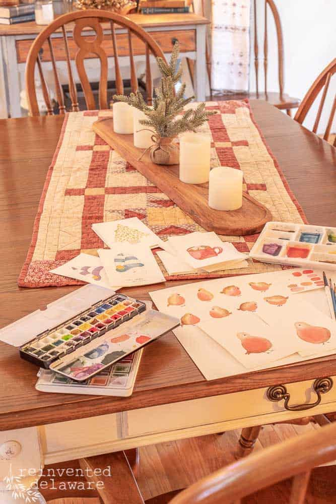 dining table with small Christmas tree and candle centerpiece with watercolor supplies
