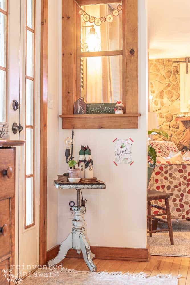 front entryway corner with vintage piano stool as a table with handmade snowmen, plant and little lamp on top