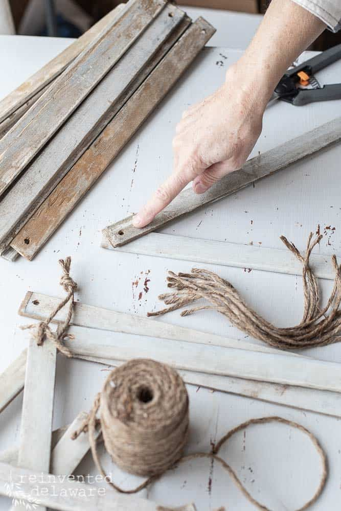 finger pointing at the hole on the handmade farmhouse style stars where the jute is used to tie the separate louvered slats together