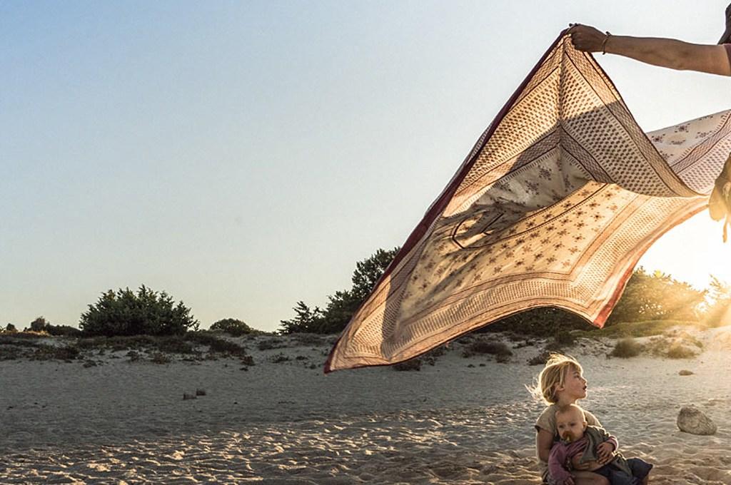 Life-for-Five-Pack-System-Papa Daniel am Strand wedelt ein Strandtuch über seine Töchter