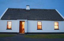 Ein irisches Cottage mit einem Strohdach am Abend.