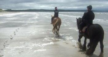 Zwei Reiter reiten an einem einsamen Strand.
