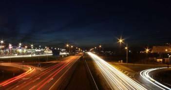 Man sieht eine Autobahn bei Nacht, fotografiert von einer Brücke aus. Es erhellen lange Lichtstreifen, da die Aufnahme mit Langzeitbelichtung erstellt wurde.
