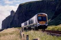 Ein Zug der irischen Bahngesellschaft auf freier Strecke. Im Hintergrund eine Felsformationen mit Klippen.