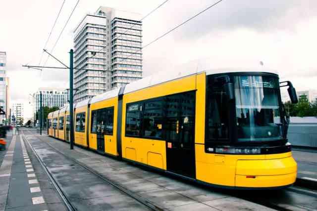 Gult U-Bahn tog ved Alexanderplatz i Berlin med højhus i baggrunden