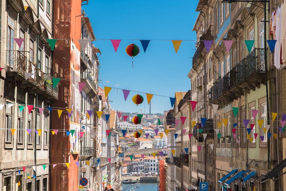 Gade i Porto med flag der er spændt ud mellem husfacaderne.
