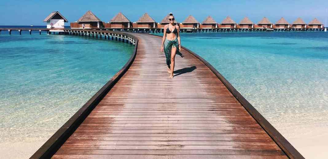 Mathilde Odgaard på Maldiverne. Går på gangbro, som løber ud i havet med hytter i baggrunden.