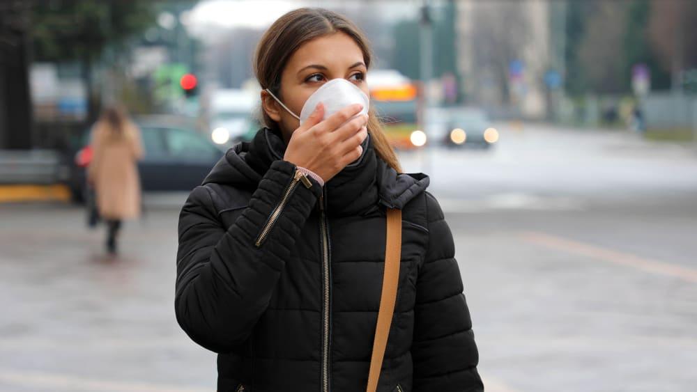 Ung kvinde der bærer ansigtsmaske i bybilledet