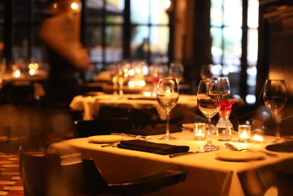Dæmpet belysning i restaurant med opdækkede borde.