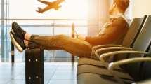 空港-寝ている男の機内持ち込み手荷物を待つ