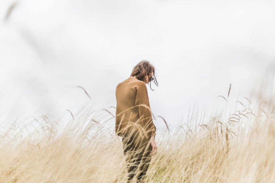 A man in a wheat field, with his head down, who sad about his relationships.