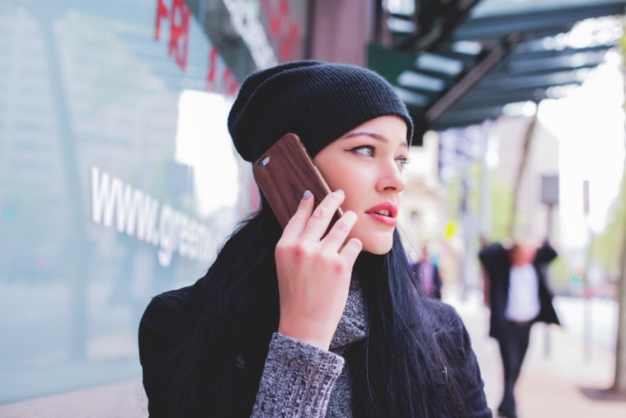woman wearing a black skull cap, talking on her cell with her men