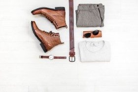 Arrangement of a men clothing. Shoes, belt, pants, white shirt, black shades, brown watch.