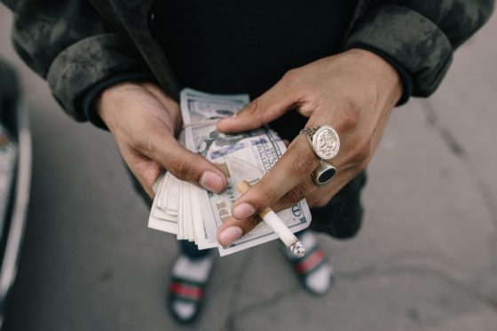 a Man preparing for a date holding his money while smoking a cigarette.