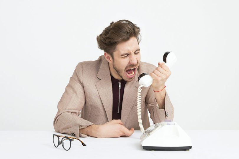 man holding telephone screaming