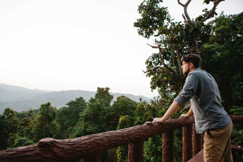 pensive young guy in solitude enjoying mountain view from wooden terrace
