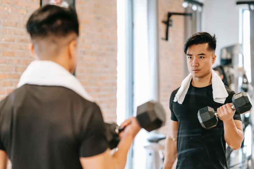 determined asian man with dumbbell in gym