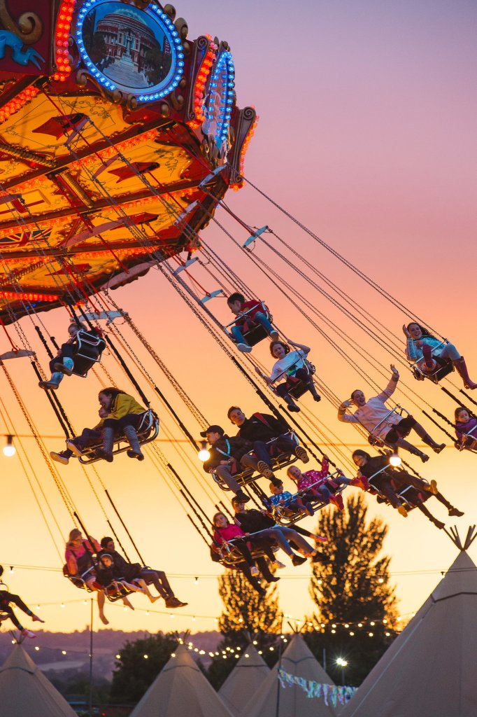 Big Feastival festival-goers on the carousel as the sun goes down