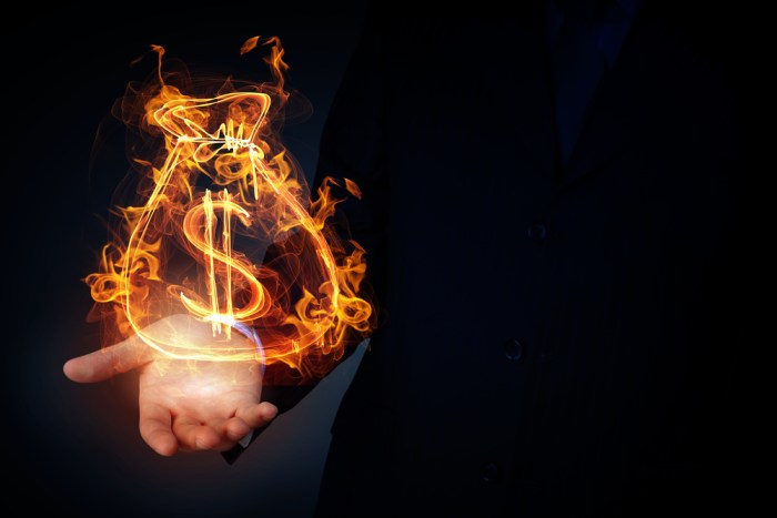 Burning dollar sign in businessman palm on dark background