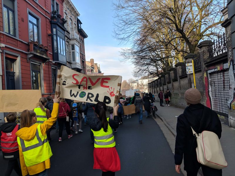 "Climate marchers in Ghent with a banner that reads ""save the world"""