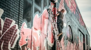 Man drawing graffiti on a wall.