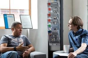 Two men talking in an office.